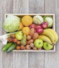 Obsthaus Mix-Kiste auf Holzboden mit allerlei Gemüse und Früchten